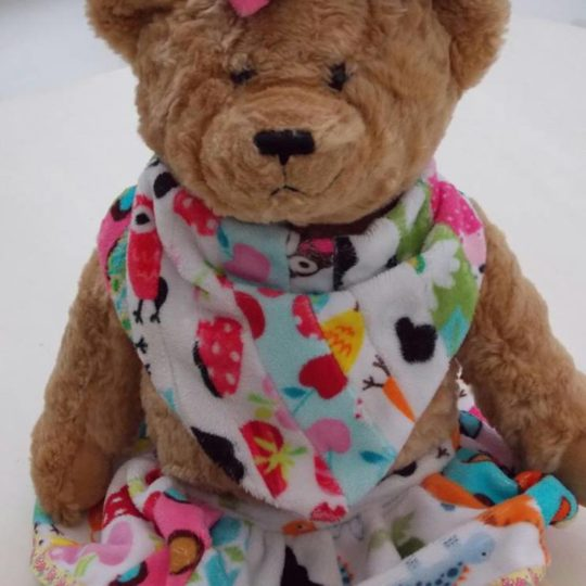Little Comforts teddy bear wearing a colourful fleece scarf.