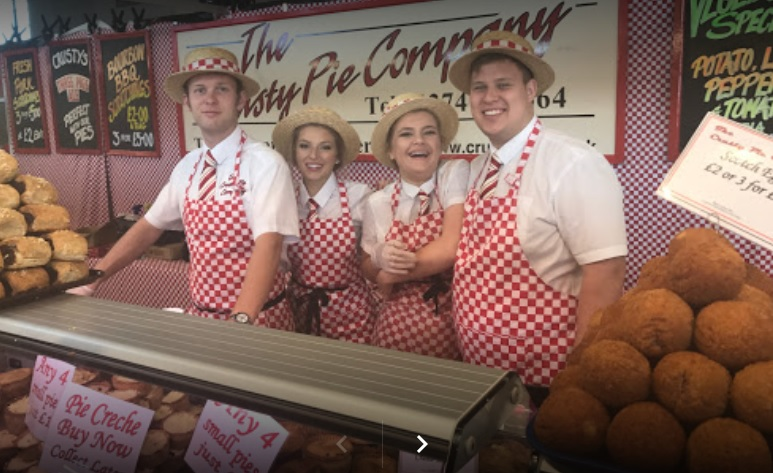 The Crusty Pie company, the ultimate pie makers, 4 traditional looking butchers pose behind their stand which is full of pies, scotch eggs and sausage rolls. They will be at the Border Union Show in July